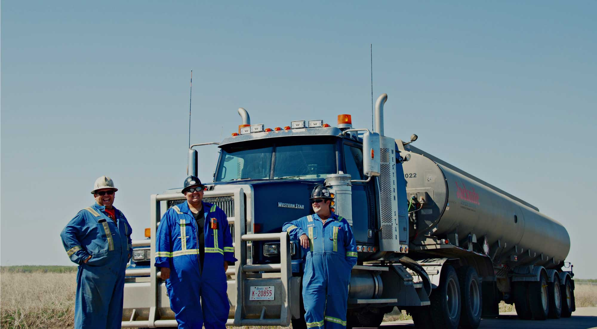 3 men with blue coveralls in front of semi truck