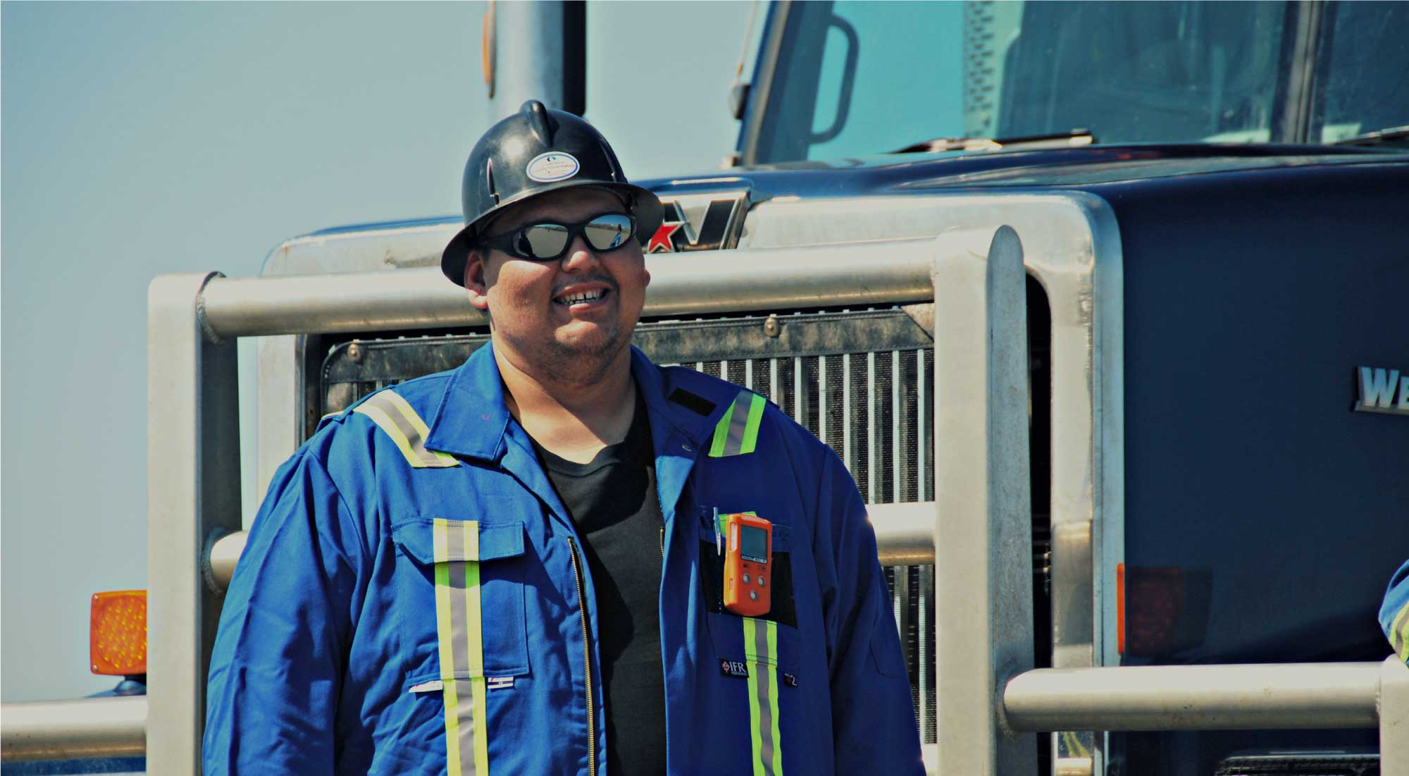 Man in blue coveralls beside a big truck
